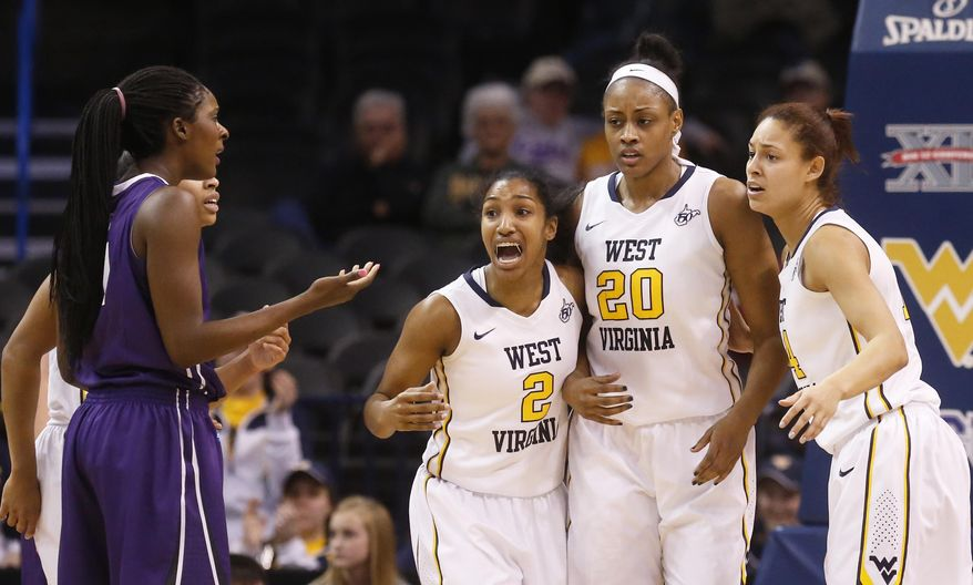 West Virginia guard Taylor Palmer (2) and forward Jess Harlee (14) congratulate Asya Bussie (20) after she was awarded a foul shot following a foul by TCU center Latricia Lovings, left, in the second half of an NCAA college basketball game in the quarterfinals of the Big 12 Conference women's tournament in Oklahoma City, Saturday, March 8, 2014. West Virginia won 67-59. (AP Photo/Sue Ogrocki)
