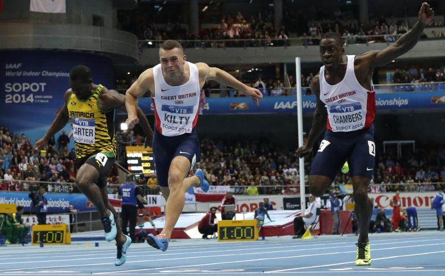 Jamaica's Nesta Carter, Britain's gold medal winner Richard Kilty and Britain's Dwain Chambers, from left, cross the line of the men's 60m final during the Athletics Indoor World Championships in Sopot, Poland, Saturday, March 8, 2014.  (AP Photo/Matt Dunham)