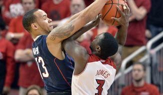 Connecticut's Shabazz Napier, left, blocks the shot of Louisville's Chris Jones during the first half of an NCAA college basketball game, Saturday, March 8, 2014, in Louisville, Ky. (AP Photo/Timothy D. Easley)