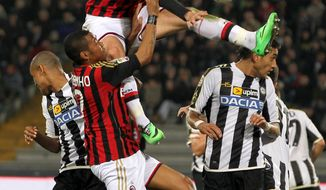 AC Milan's Giampaolo Pazzini, top, jumps over his teammate Robinho as he reaches for the ball during the Serie A soccer match between Udinese and Milan at the Friuli Stadium in Udine, Italy, Saturday, Mar. 8, 2014. (AP Photo/Paolo Giovannini)
