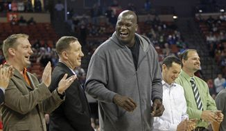 Former NBA star Shaquille O'Neal laughs with his former high school teammates during halftime of the boys' UIL Class 1A Division 1 state basketball final, Saturday, March 8, 2014, in Austin, Texas. The UIL was honoring the undefeated 1989 San Antonio Cole Team (36-0) that won the state championship 25 years ago.  O'Neal was described as the greatest player to ever play in the UIL State Tournament by UIL Executive President Charles Breithaupt. (AP Photo/Michael Thomas)