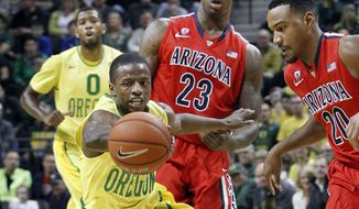 As Oregon's Mike Moser looks on, rear left, teammate Johnathan Loyd battles Arizona's Rondae Hollis-Jefferson and Jordin Mayes, right, for a loose ball during the first half of an NCAA college basketball game in Eugene, Ore. on Saturday, March 8, 2014. (AP Photo/Chris Pietsch)