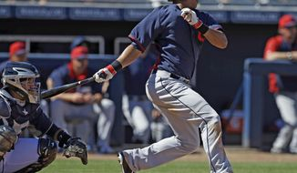 Cleveland Indians' Michael Brantley (23) singles as San Diego Padres catcher Rene Rivera watches during the third inning of an exhibition spring training baseball game Saturday, March 8, 2014, in Peoria, Ariz. (AP Photo/Darron Cummings)