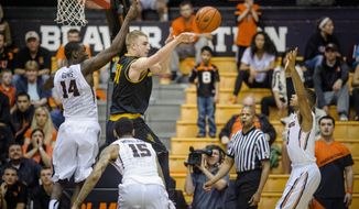 Arizona State's Jonathan Gilling center, passes the ball past Oregon State's Daniel Gomis, left, Eric Moreland, center, and Hallice Cooke, right during the second half of an NCAA college basketball game in Corvallis, Ore., Saturday March 8 2014. Oregon State won the game 78-76.(AP Photo/Karl Maasdam)