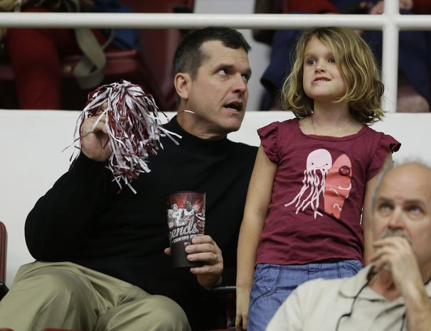 San Francisco 49ers head coach Jim Harbaugh sits with his 5-year-old daughter, Addison, during halftime of Stanford's NCAA college basketball game against Utah on Saturday, March 8, 2014, in Stanford, Calif. (AP Photo/Eric Risberg)