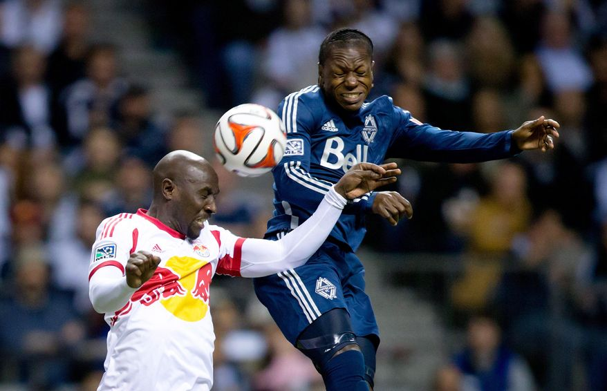 New York Red Bulls' Ibrahim Sekagya, left, of Uganda, and Vancouver Whitecaps' Darren Mattocks, of Jamaica, vie for the ball during first half MLS soccer game action in Vancouver, B.C., on Saturday March 8, 2014.  (AP Photo/The Canadian Press, Darryl Dyck)