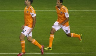 Houston Dynamo forward Will Bruin (12) celebrates the first of his two goals in the first period with midfielder Tony Cascio (28) during an MLS soccer game against the New England Revolution, Saturday, March 8, 2014, in Houston. (AP Photo/ The Courier, Jason Fochtman) MANDATORY CREDIT