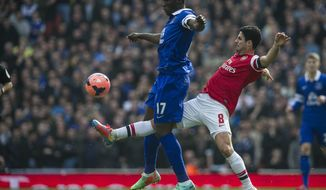 Arsenal's Mikel Arteta, fights for the ball with Everton's Romelu Lukaku, during their FA Cup quarterfinal soccer match, at Emirates Stadium, in London, Saturday, March 8, 2014. (AP Photo/Bogdan Maran)