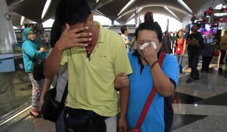 A woman wipes her tears after walking out of the reception center and holding area for family and friend of passengers aboard a missing Malaysia Airlines plane, at Kuala Lumpur International Airport in Sepang, outside Kuala Lumpur, Malaysia, Saturday, March 8, 2014. Search teams across Southeast Asia scrambled on Saturday to find a Malaysia Airlines Boeing 777 with 239 people on board that disappeared from air traffic control screens over waters between Malaysia and Vietnam early that morning. (AP Photo/Lai Seng Sin)