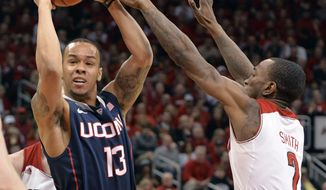 Connecticut's Shabazz Napier, left, looks for help from the defense of Louisville's Russ Smith during the first half of an NCAA college basketball game, Saturday, March 8, 2014, in Louisville, Ky. (AP Photo/Timothy D. Easley)