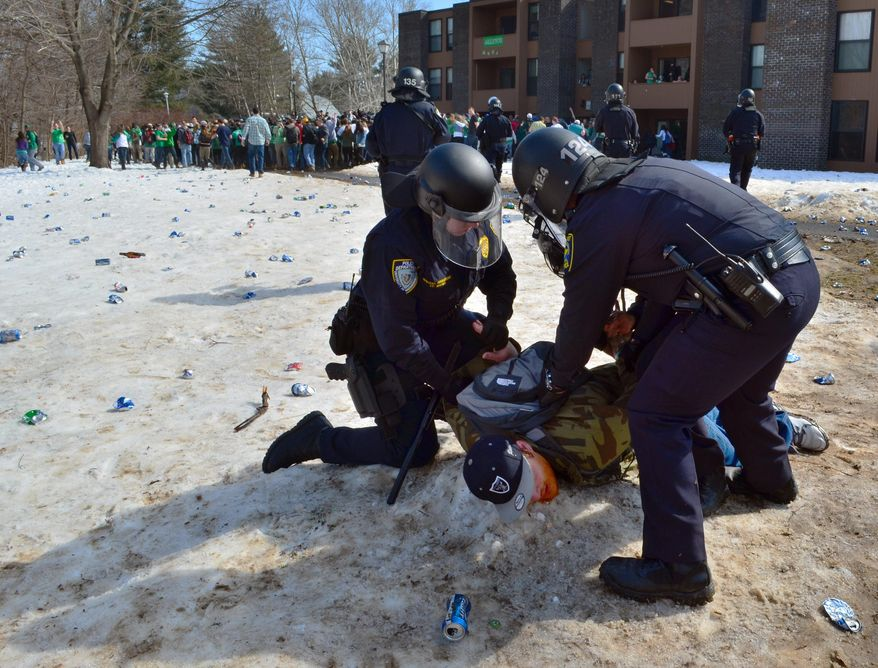 """Police detain a participant in the pre-St. Patrick's Day """"Blarney Blowout"""" near the University of Massachusetts in Amherst, Mass. on Saturday, March 8, 2014. According to the Amherst police department, four police officers were hurt as they worked to disperse hundreds of unruly students who were throwing beer cans and bottles at police on Saturday as large crowds gathered at the off-campus apartment complex. Police in riot gear arrested 35 at the event. (AP Photo/The Republican, Robert Rizzuto)"""