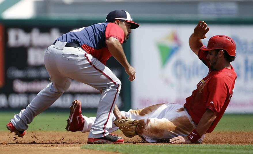 St. Louis Cardinals' Matt Carpenter, right, is tagged out while trying to steal second base by Washington Nationals' Anthony Rendon, left, during the first inning of an exhibition spring training baseball game, Saturday, March 8, 2014, in Jupiter, Fla. (AP Photo/David Goldman)