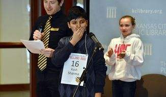 """Kush Sharma, center, reacts after spelling """"definition"""" to win the Jackson County Spelling Bee in the 29th round at the Central Library, as Sophia Hoffman, right, looks on, in Kansas City, Mo., Saturday, March 8, 2014. Two weeks ago, the bee ran out of words after the two eliminated 23 other contestants and went another 47 rounds against each other. (AP Photo/The Kansas City Star, Jill Toyoshiba)"""