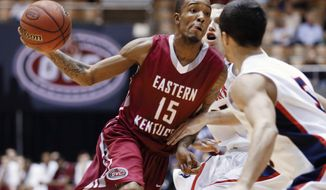 Eastern Kentucky guard Orlando Williams (15) drives against Belmont defenders Evan Bradds, center, and Caleb Chowbay (5) during the first half of an NCAA college basketball game for the championships of the Ohio Valley Conference men's tournament, Saturday, March 8, 2014, in Nashville, Tenn. (AP Photo/Mark Humphrey)