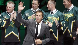 Former Dallas Stars player Mike Modano waves to the crowd during a jersey retirement ceremony before the Stars played the Minnesota wild in an NHL hockey game in Dallas on Saturday, March 8, 2014. (AP Photo/Richard W. Rodriguez)