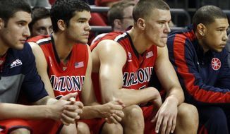 Arizona;s Elliot Pitts, center left, and Kaleb Tarczewski, center right, watch from the bench as Oregon moves ahead in the second half of an NCAA college basketball game in Eugene, Ore. on Saturday, March 8, 2014. (AP Photo/Chris Pietsch)