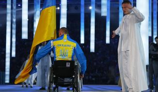 Biathlete Mykhaylo Tkachenko, representing Ukraine, enters the arena during the opening ceremony of the 2014 Winter Paralympics at the Fisht Olympic stadium in Sochi, Russia, Friday, March 7, 2014. (AP Photo/Dmitry Lovetsky)