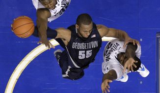 Georgetown's Jabril Trawick, center, goes up for a shot against Villanova's James Bell, left, and JayVaughn Pinkston during the second half of an NCAA college basketball game, Saturday, March 8, 2014, in Philadelphia. Villanova won 77-59. (AP Photo/Matt Slocum)