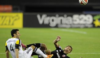 Columbus Crew defender Michael Parkhurst (4) and D.C. United midfielder Davy Arnaud, right, look for the ball during the second half of an MLS soccer game, Saturday, March 8, 2014, in Washington. Columbus won 3-0. (AP Photo/Nick Wass)