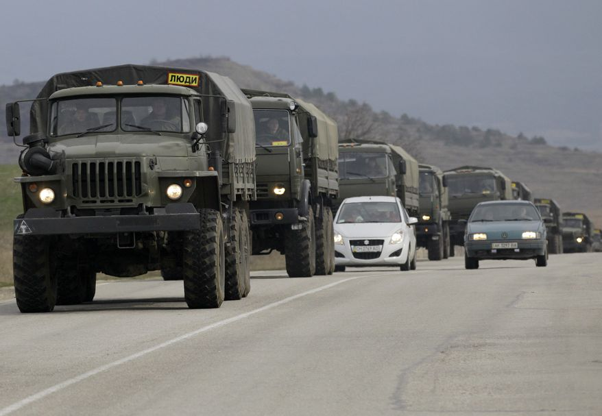 A convoy of military vehicles bearing no license plates travels on the road from Feodosia to Simferopol in the Crimea, Ukraine, Saturday, March 8, 2014. More than 60 military trucks bearing no license plate numbers was headed from the eastern city of Feodosia toward the city of Simferopol, the regional capital. (AP Photo/Darko Vojinovic)
