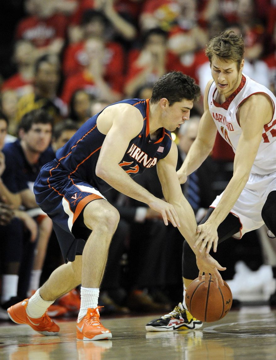 Maryland's Jake Layman, right, battles for the ball against Virginia guard Joe Harris, left, during the second half of an NCAA college basketball game, Sunday, March 9, 2014, in College Park, Md. Maryland won 75-69 in overtime. (AP Photo/Nick Wass)