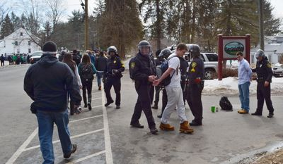 """Police detain participants in the pre-St. Patrick's Day """"Blarney Blowout"""" near the University of Massachusetts in Amherst, Mass. on Saturday, March 8, 2014. Amherst police said early Sunday that 73 people had been arrested after authorities spent most of the day Saturday attempting to disperse several large gathering around the UMass campus for the party traditionally held the Saturday before spring break. The partying carried through Saturday evening into early Sunday, and Amherst Police Capt. Jennifer Gundersen said in a statement that police were busy with numerous reports of fights, noise and highly intoxicated individuals.(AP Photo/The Republican, Robert Rizzuto)  MANDATORY CREDIT"""