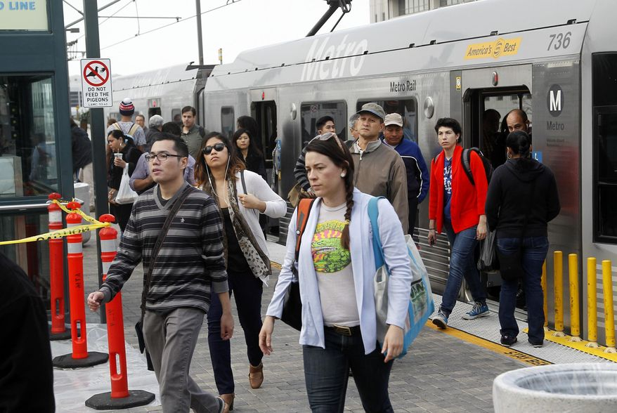 Pedestrians disembark from a train at Union Station Friday March 7, 2014 in Los  Angeles. Americans are boarding public buses, trains and subways in greater numbers than any time since the suburbs began to boom. Nearly 10.7 billion trips in 2013, to be precise, the highest number since 1956.  (AP Photo/Nick Ut)
