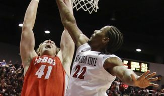 New Mexico forward Cameron Bairstow scores against the defense of San Diego State forward Josh Davis during the first half of a NCAA college basketball game Saturday, March 8, 2014, in San Diego. (AP Photo/Lenny Ignelzi)