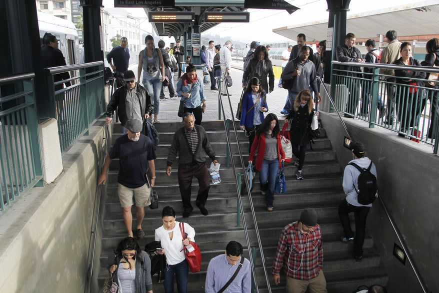Pedestrians prepare to board a train at Union Station Friday March 7, 2014 in Los  Angeles. Americans are boarding public buses, trains and subways in greater numbers than any time since the suburbs began to boom. Nearly 10.7 billion trips in 2013, to be precise, the highest number since 1956.  (AP Photo/Nick Ut)