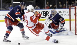 New York Rangers' John Moore (17) checks Detroit Red Wings' Drew Miller (20) as goalie Henrik Lundqvist (30), of Sweden, watches during the first period of an NHL hockey game on Sunday, March 9, 2014, in New York. (AP Photo/Frank Franklin II)