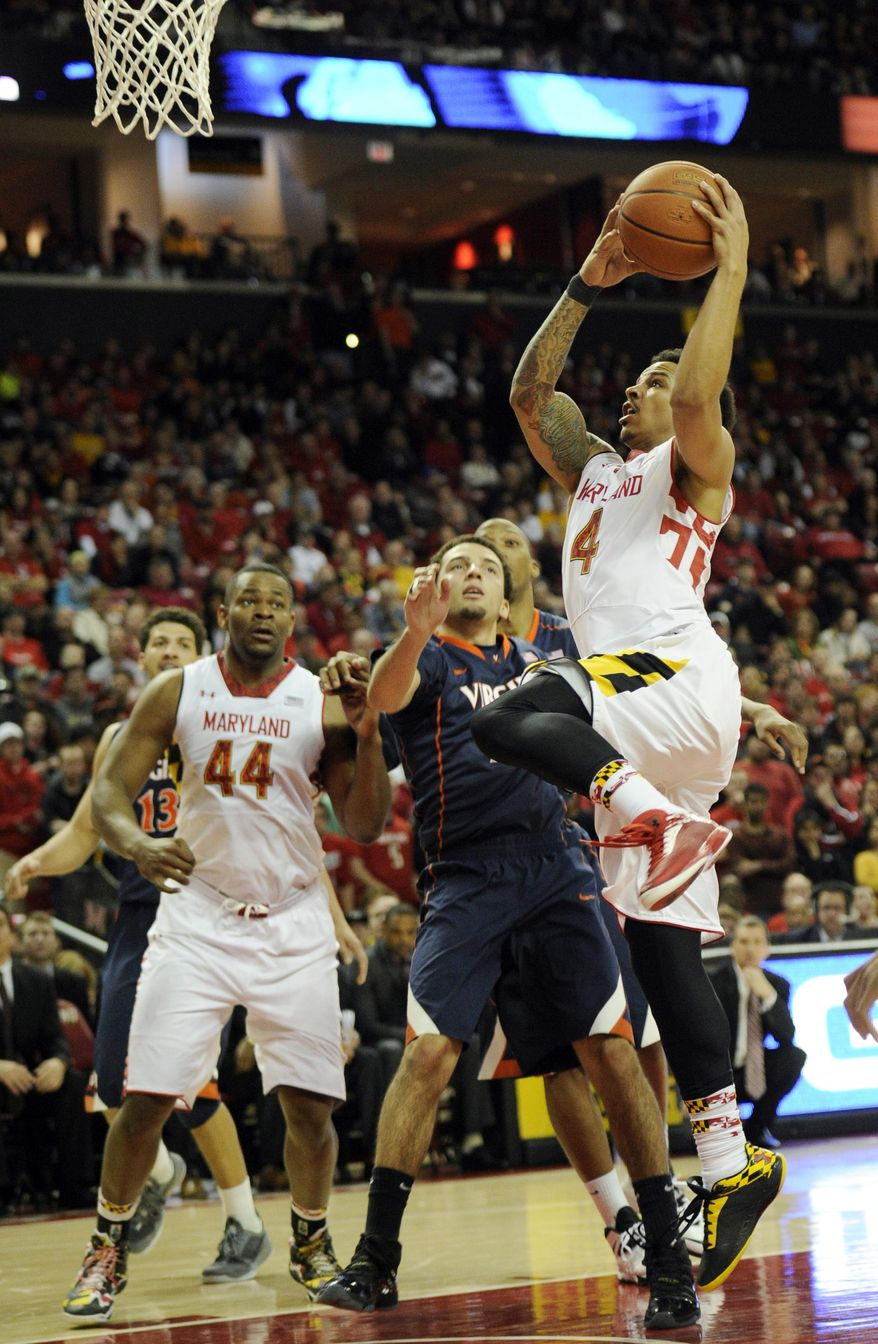 Maryland guard Seth Allen (4) goes to the basket against Virginia guard London Perrantes, center, during overtime of an NCAA college basketball game, Sunday, March 9, 2014, in College Park, Md. Maryland won 75-69. Also seen is Maryland center Shaquille Cleare (44). (AP Photo/Nick Wass)