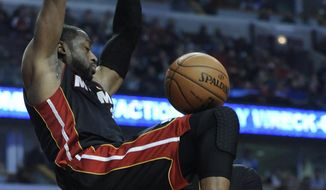 Miami Heat's Dwyane Wade dunks during the first quarter of an NBA basketball game against the Chicago Bulls in Chicago, Sunday, March 9, 2014. (AP Photo/ Paul Beaty)
