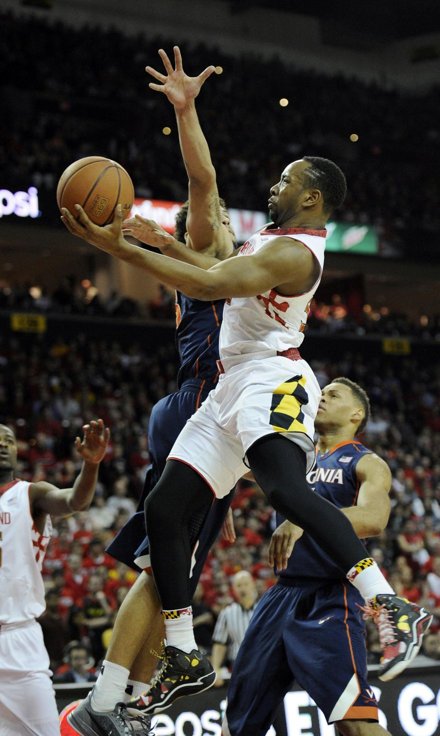 Maryland's Dez Wells, center, goes to the basket against Virginia forward Anthony Gill, left, and Justin Anderson, right, during the second half of an NCAA college basketball game, Sunday, March 9, 2014, in College Park, Md. Maryland won 75-69 in overtime. (AP Photo/Nick Wass)