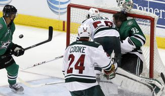 Minnesota Wild left wing Erik Haula (56) collides with Dallas Stars goalie Kari Lehtonen (32), who loses his helmet during the third period an NHL hockey game in Dallas Saturday, March 8, 2014. The Stars won 4-3. (AP Photo/Richard W. Rodriguez)