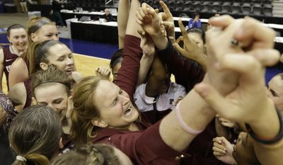 Fordham head coach Stephanie Gaitley, center, celebrates with her team after winning the A10 women's basketball championship game against Dayton in Richmond, Va., Sunday, March 9, 2014. Fordham defeated Dayton 63-51. (AP Photo/Steve Helber)