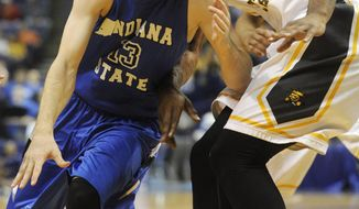 CORRECTS TO WICHITA STATE'S CHADRACK LUFILE (0) NOT CLEANTHONY EARLY (11) - Indiana State's Jake Odum (13) drives on Wichita State's Chadrack Lufile (0) in the first half of an NCAA college basketball game in the championship of the Missouri Valley Conference men's tournament on Sunday, March 9, 2014, in St. Louis. (AP Photo/Bill Boyce)