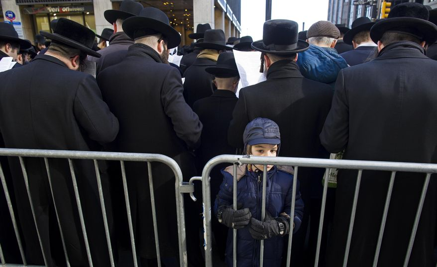 A young boy stands along a barricade as Orthodox Jews gather in New York, Sunday, March 9, 2014, on Water Street in lower Manhattan, to pray and protest against the Israeli government's proposal to pass a law that would draft strictly religious citizens into its army. (AP Photo/Craig Ruttle)