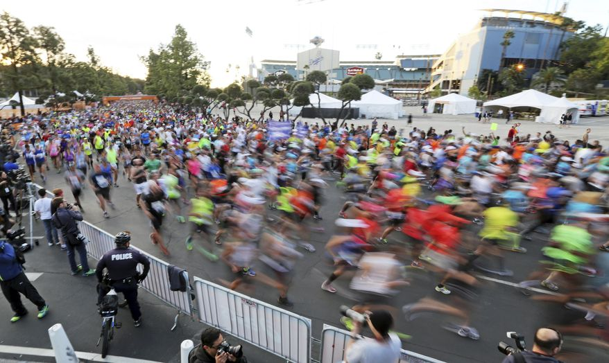 Runners in the Los Angeles Marathon take off from Dodger Stadium in Los Angeles, Sunday, March 9, 2014. (AP Photo/Reed Saxon)