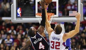 Atlanta Hawks forward Paul Millsap (4) and Los Angeles Clippers forward Blake Griffin (32) reach for a rebound in the first half of an NBA basketball game, Saturday, March 8, 2014, in Los Angeles. (AP Photo/Gus Ruelas)