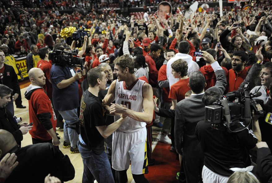 Maryland's Jake Layman (10) celebrates with the crowd after fans rushed the floor after beating Virginia 75-69 in overtime of an NCAA college basketball game, Sunday, March 9, 2014, in College Park, Md. (AP Photo/Nick Wass)