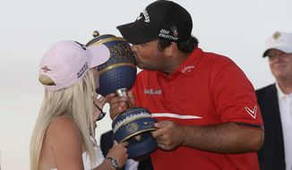 Patrick Reed  and his wife Justine kiss The Gene Sarazen trophy after Reed won the Cadillac Championship golf tournament Sunday, March 9, 2014, in Doral, Fla. (AP Photo/Wilfredo Lee)