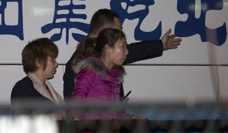 A Chinese police man guides relatives of Chinese passengers aboard a missing Malaysia Airlines plane as they arrive at the Exit and Entry Administration of the Public Security Bureau, a police department in charge of issuing passports in Beijing, China, Sunday, March 9, 2014. (AP Photo/Ng Han Guan)