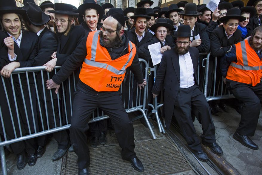 Barricades are secured as thousands of Orthodox Jews gathered in New York, Sunday, March 9, 2014, on Water Street in lower Manhattan, to pray and protest against the Israeli government's proposal to pass a law that would draft strictly religious citizens into its army. (AP Photo/Craig Ruttle)