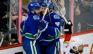 Vancouver Canucks' Yannick Weber, left, of Switzerland, and Tom Sestito celebrate Weber's goal as Calgary Flames' Brian McGrattan, right, looks on during third period NHL hockey action in Vancouver, British Columbia on Saturday March 8, 2014. (AP Photo/The Canadian Press, Darryl Dyck)