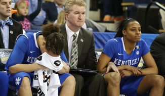 Kentucky guard Makayla Epps, left, sits on the bench with assistant coach Jeff House and teammate Bria Goss, right, in the finals moments of the second half of an NCAA college basketball game against Tennessee  in the finals of the Southeastern Conference women's basketball tournament Sunday, March 9, 2014, in Duluth, Ga. Tennessee  won 71-70. (AP Photo/Jason Getz)