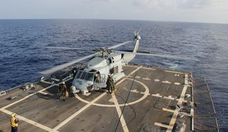 A U.S. Navy helicopter lands aboard Destroyer USS Pinckney during a crew swap before returning to a search and rescue mission for the missing Malaysian airlines flight MH370 in the Gulf of Thailand, Sunday, March 9, 2014. The plane, which was carrying 239 people, lost contact with ground controllers somewhere between Malaysia and Vietnam after leaving Kuala Lumpur early Saturday morning for Beijing. (AP Photo/Navy Media Content Service, Senior Chief Petty Officer Chris D. Boardman)
