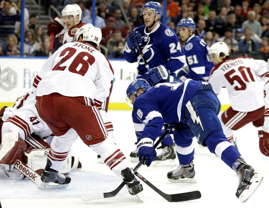 Tampa Bay Lightning left wing Ondrej Palat, of the Czech Republic, shoots the puck past Phoenix Coyotes goalie Mike Smith (41) and defenseman Michael Stone (26) for a goal after taking a pass from Lightning's Ryan Callahan (24) during the second period of an NHL hockey game, Monday, March 10, 2014, in Tampa, Fla. (AP Photo/Chris O'Meara)