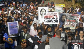 """Hundreds of marchers waive their signs as they walk to the Florida Capitol Monday, March 10, 2014, for a rally in Tallahassee, Fla. Participants were rallying against the state's """"Stand Your Ground"""" laws. (AP Photo/Phil Sears)"""