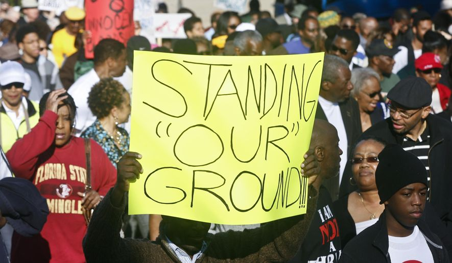"Marchers hold up their signs as they walk to the Florida Capitol Monday, March 10, 2014, for a rally in Tallahassee, Fla. Participants were rallying against the state's ""Stand Your Ground"" laws. (AP Photo/Phil Sears)"