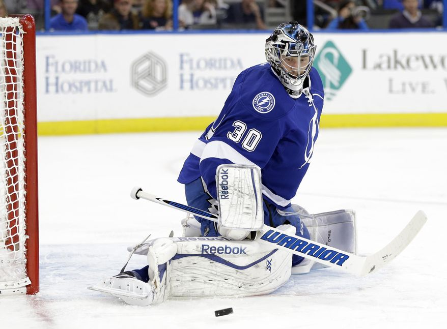 Tampa Bay Lightning goalie Ben Bishop (30) kicks aside a shot by the Phoenix Coyotes during the first period of an NHL hockey game, Monday, March 10, 2014, in Tampa, Fla. (AP Photo/Chris O'Meara)